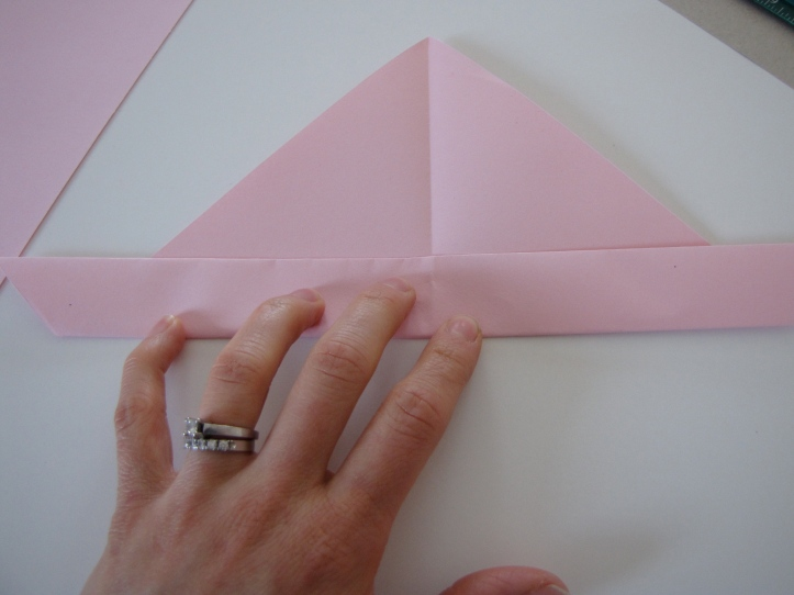 Fold up the long edge of the triangle.