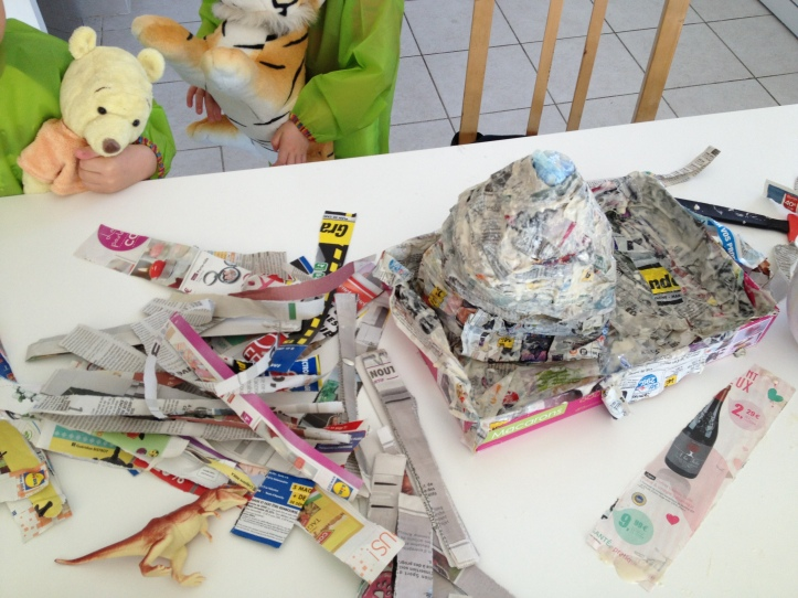Once you have the volcano shape that you want, dip strips of paper into your homemade glue and over up your volcano and its surrounding area.